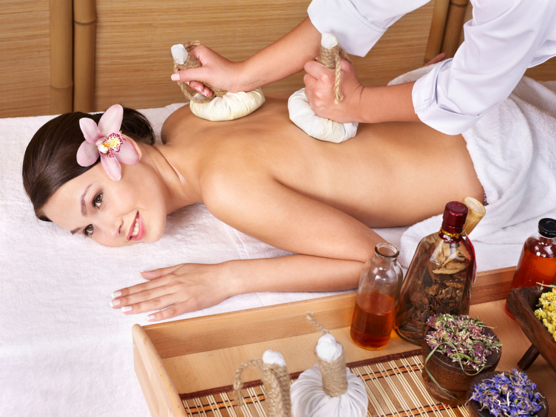Young woman on massage table in beauty spa -- The Luxury Signature